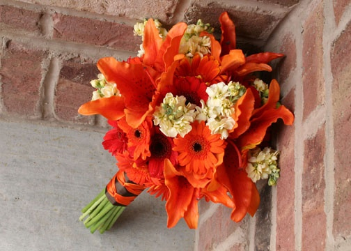 Orange and brown wedding flowers.  This bouquet is fun, with the tiger lilies and orange gerber daisies, I can't help but smile.  The ribbon striped handle added just a touch of style.