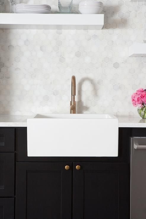 Chic black and white kitchen features black cabinets adorned with aged brass knobs paired with white quartz countertops, Silestone Bianco Orion, and a white marble hexagon tile backsplash. A small apron sink and brass high arc faucet stands under staggered white floating shelves.