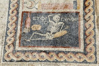 """Greek mosaic of 'cheerful' skeleton found in Turkey.  Turkey's state-run news agency says archaeologists have unearthed an ancient mosaic featuring a reclining skeleton holding a drink with the inscription in Greek: """"Be cheerful, enjoy life."""" The mosaic was discovered in the ancient city  of Antiocheia [Credit: AA]"""