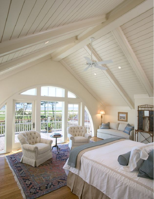 master bedroom with lofty beamed ceilings and arched window wall with ocean view