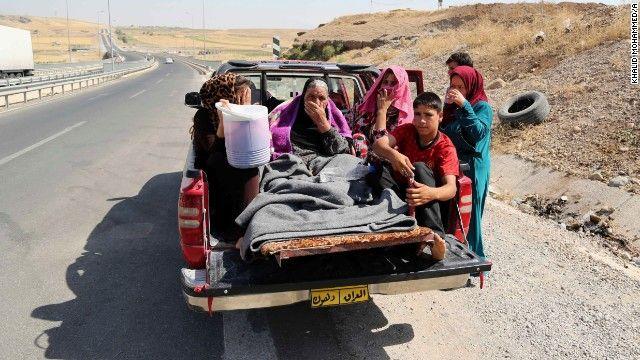 Iraquianos deslocados montar em um caminhão em uma estrada montanhosa perto da fronteira com a Turquia eo Iraque, fora Dahuk, no dia 9 de agosto.