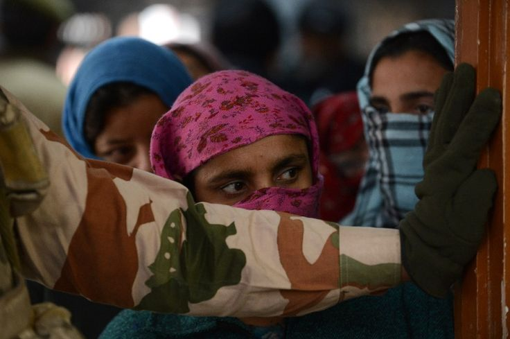Indo-Tibetan Border Police stand guard as Kashmiri voters queue at a polling station in SrinagarIndo-Tibetan Border Police stand guard as Kashmir...