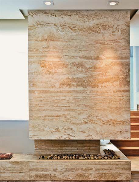 A peça é fechada com mármore travertino navona, mesmo acabamento da base. Na parte interna, tijolo refratário. Lareira de canto a gás