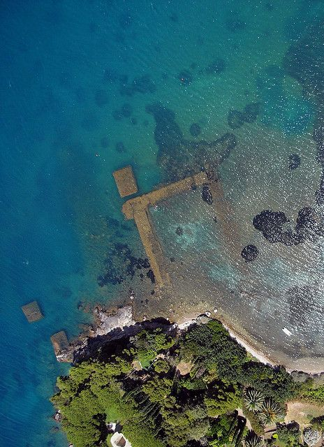 Sunken Roman ruins of Villa Domizia by opaxir on Flickr.  During the Punic Wars (264-146 BC), this area in Tuscany was acquired by the Enobarbi Domizi family, wealthy Romans who loaned money to the Roman Republic during the wars. They recieved the promontory as payment for the debts and it was renamed after the family.  These sunken ruins are on the peninsula of Monte Argentario, Grosseto Province, Tuscany, Italy.
