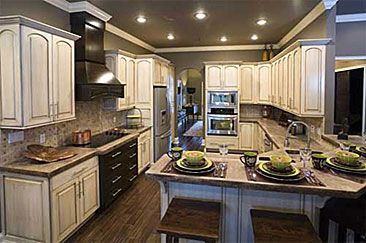The G-shaped kitchen is very similar to the U-shaped kitchen layout, except that it includes a peninsula or partial fourth wall for additional cabinets. Depending on the size and design of the kitchen floor plan, a G-shaped kitchen can feel cramped. It's a good idea to open up a wall to overlook the living, dining or breakfast room.
