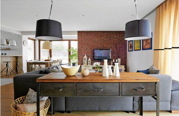 Za kanapą stoi metalowa konsolka z drewnianym blatem - kolejny mebel kupiony przez Annę okazyjnie w internecie. Zazwyczaj są na niej eksponowane dekoracyjne drobiazgi, ale okazjonalnie służy także jako biurko. Wtedy wiszące nad kanapą lampy są tak ustawiane, by światło padało na blat.