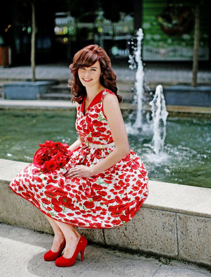 Alice má na sobě šaty ušité podle originální střihu z 50. let se vzorem vlčích máků od Lazy Eyes. Květinový klobouk, Jane Bond. Červené lodičky z kolekce Vivienne Westwood for Melissa prodává Bella Brutta.