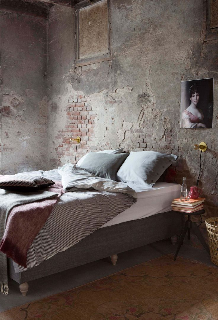 Donkere industriële slaapkamer met kussens en plaids   Dark industrial bedroom…