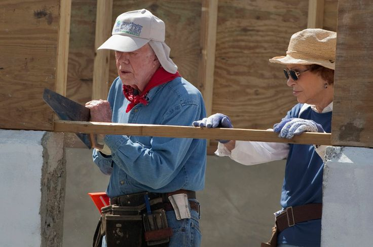 Former U.S. President Jimmy Carter uses a saw, working on a home as his wife Rosalynn helps while they visit a Habitat for Humanity project in Leogane, Haiti, on November 7, 2011. The Carters joined volunteers from around the world to build 100 homes in partnership with earthquake-affected families in Haiti during a week-long Habitat for Humanity housing project.