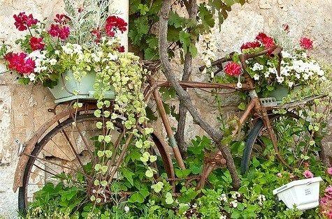 Idée récup pour votre jardin : Un vieux vélo peut servir de support pour exposer ses jardinières au jardin, agrémenté de jolies fleurs, voilà une déco originale.
