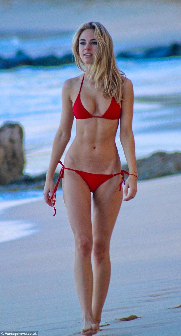Red hot: Kimberley Garner showed off her envy-inducing figure in a red bikini on Wednesday as she strolled along the beach in the Caribbean