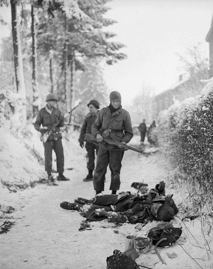 American soldiers stop to look at the frozen corpses of German soldiers killed during the Battle of the Bulge - January 1945.