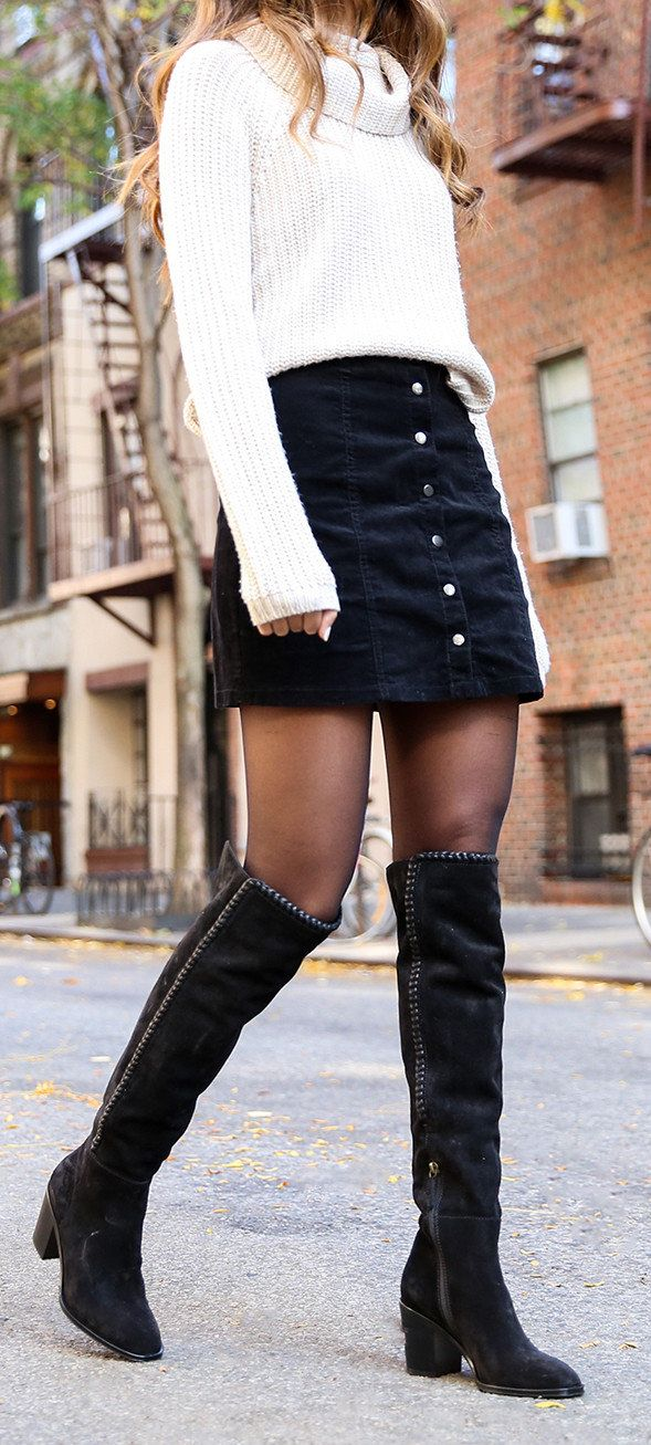 #fall #outfits women's beige knitted cowl neckline sweater, black mini skirt and black studded knee-high chunky heeled boots outfit