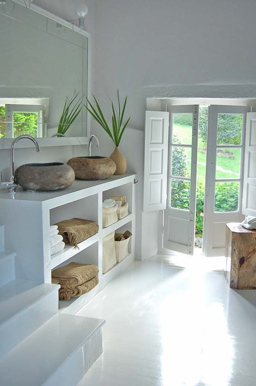 Loving the natural stone sink vessels, the crisp white space, and petrified wood stool