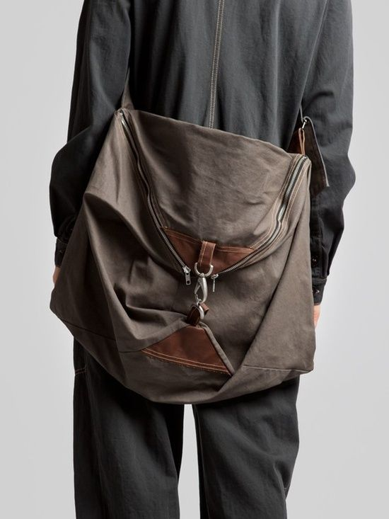 angled canvas bag with leather, zipper, and buckle accents