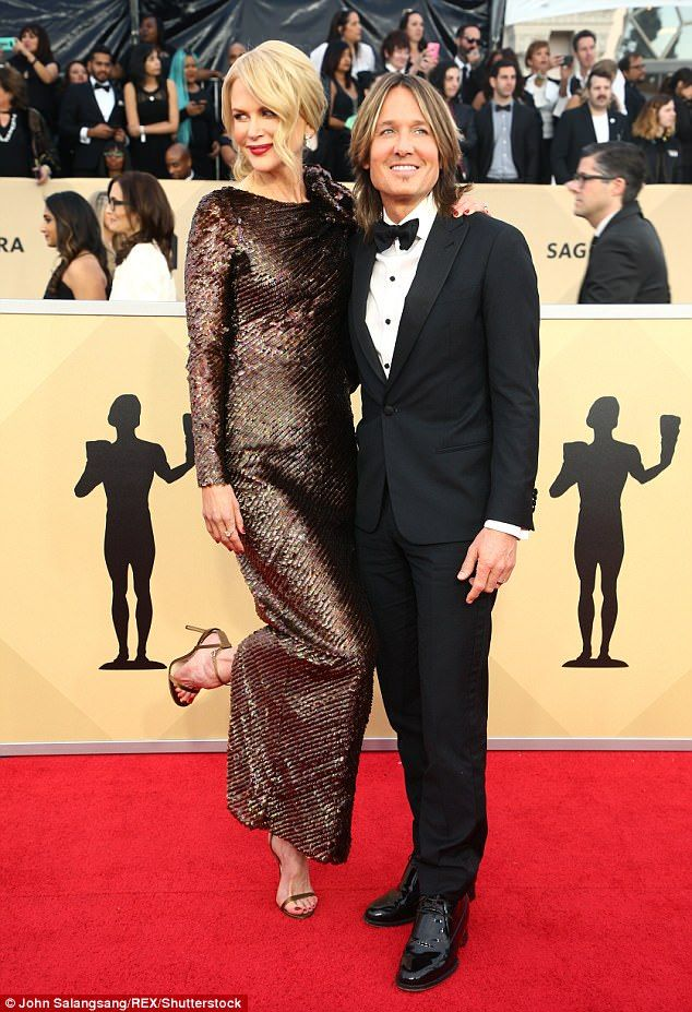 Loved-up: The high-profile pair put on an amorous display as they posed for the cameras...