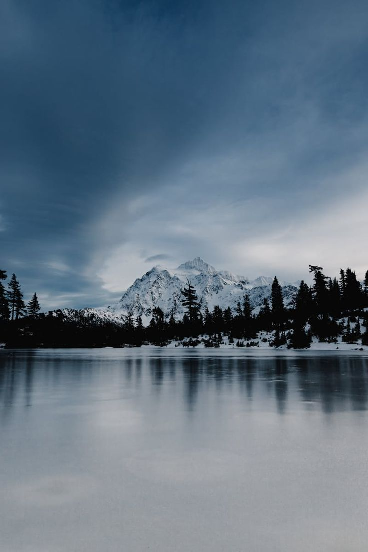 Landscape of Blue White Cloudy Sky Above Semi-frozen Lake Bordered by Forest