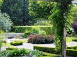 De tuin heeft een eigentijds karakter van strakke lijnen en hagen,maar met natuurlijk ogende en losse beplanting. Zo is er een prairieborder met prachtige siergrassen ,die tot diep in de herfst zijn kleuren toont. De vijvertuin is een paradijs voor de vele kikkers, libellen en vlinders. U kunt wandelen door een laantje van dakiepen en op diverse zitplekken is het heerlijk toeven in de zon of in de schaduw.