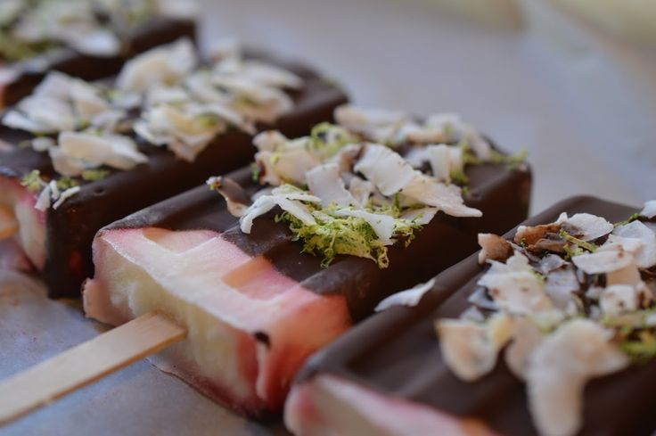 Raspberry and yogurt ice pops get all dressed up with organicfair 70% purist chocolate dip and finished with our coconut slices and lime zest.