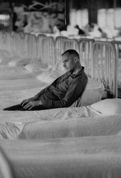A schizophrenic patient depressed & withdrawn, sitting beside his ward bed, at Wayne County Hosp.