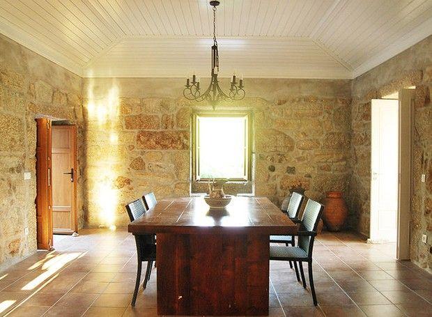 Sala de jantar da casa principal. Uma das fortes características desse projeto são as rústicas paredes de granito, preservadas da obra original (Foto: Divulgação)