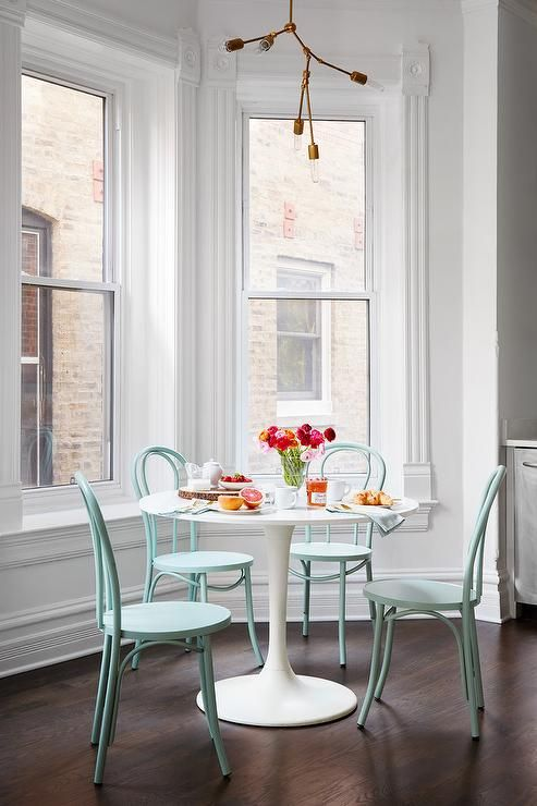 In front of uncovered bay windows, a white pedestal dining table is lit by a modern modular light pendant and surrounded by aqua Thonet Bentwood Chairs.