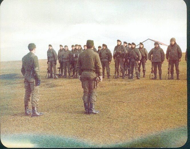 25 Mayo 1982 --- Integrantes del grupo de combate Güemes, que combatieron en San Carlos el 21 de Mayo, cantan el Himno Nacional en Douglas Paddle. De espaldas se ven al Subteniente José Vázquez (izquierda) y al Teniente 1ro Esteban.