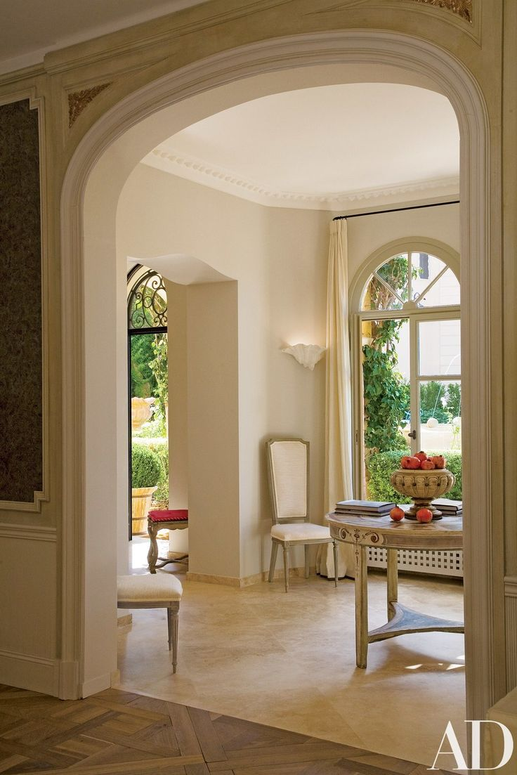"""In the anteroom off the entrance hall, Haslam installed an antiqued-stone floor and a plaster cornice, with an overscale egg motif he created. """"The space is an exercise in restraint, with just a splash of color and pattern,"""" he points out. The painted table is Italian; the high-back chairs are French."""