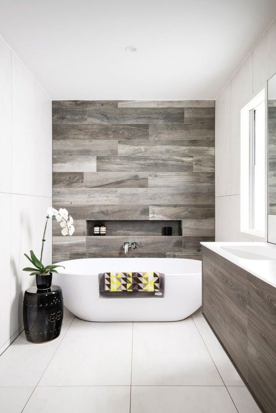 a contemporary bathroom with reclaimed wood touches and negative space for a comfy feel