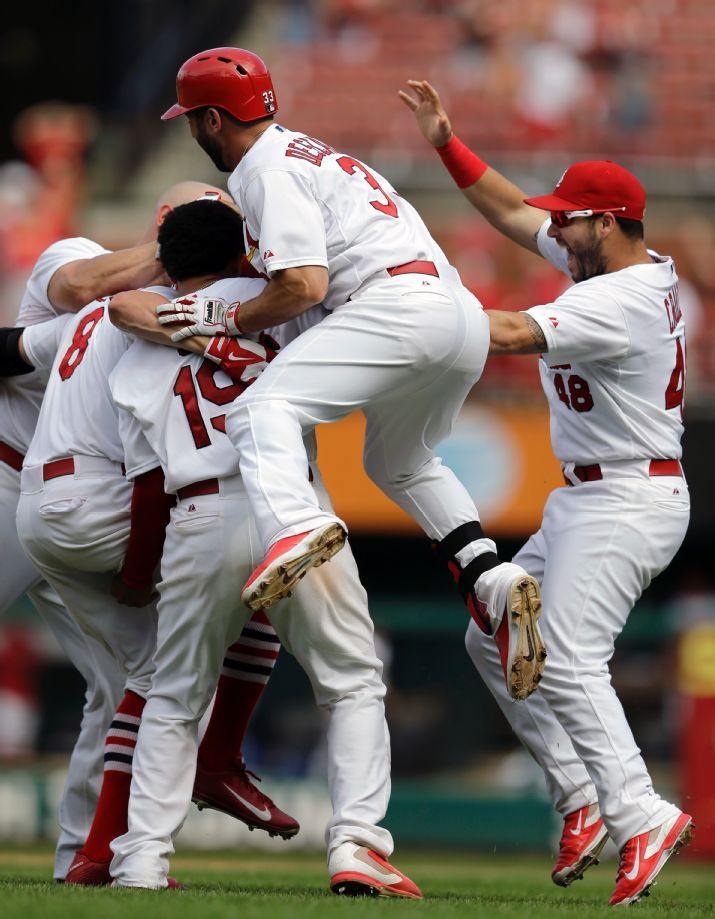 St. Louis Cardinals' Peter Bourjos (8) is congratulated by teammates after hitting a walkoff-single to score Yadier Molina during the ninth ...