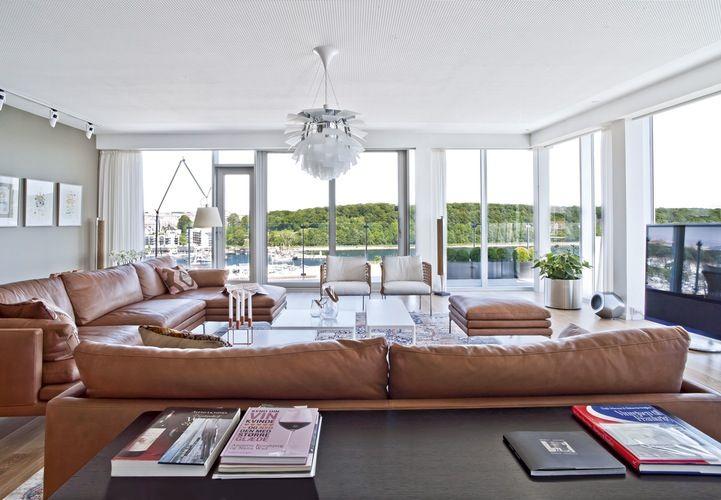 """Den store sofagruppe er bygget op af William-sofaer fra Zanotti med ben i poleret aluminium, som får dem til at """"svæve"""". Sofaborde med plader af Carrera-marmor er placeret, så man nemt kommer omkring. Konsolbordene er fra DePadova. Lænestolene hedder Café og er fra Living Divani. PH's Koglen og Tolomeo Mega fra Artemide giver lys. De nye Beolab 18-højttalere fra B&O blender fint ind uden at skjule sig."""