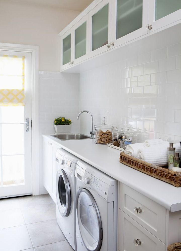 A beautiful bright, white laundry room with glistening subway tile and counter space to boot!