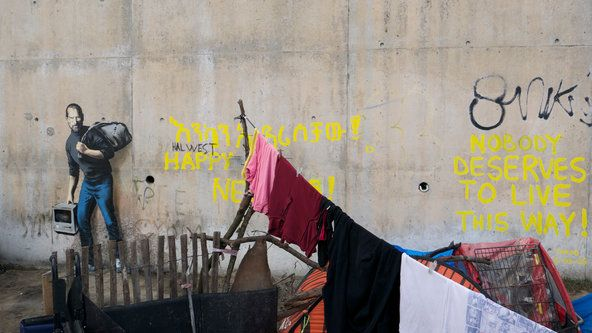 """The graffiti artist Banksy unveiled his latest artworks on Friday — immigration-themed murals that he painted onto public spaces in and around the """"jungle,"""" a refugee camp near Calais, France. (Photo:  banksy.co.uk)"""