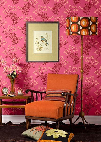 Pink and red wallpaper against orange armchair, via Design Amour