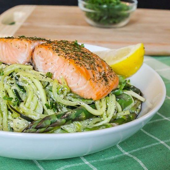"Fresh dill, asparagus, citrus, and zucchini come together to create a bed of creamy dill pasta for a piece of wild-caught salmon. If you don't have a spiralizer to make your own zucchini noodles, then take a tip from this Paleo ""pasta,"" and julienne the zucchini instead."