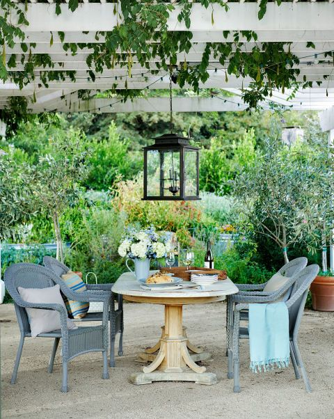 Wicker chairs from Target pull up to an antique pine table under a wisteria-covered pergola of this California garden. Olive trees border either side of the gravel patio.