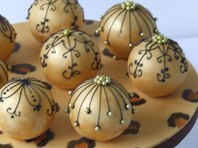 Bauble birthday cake ~ eight little bauble cakes in gold with black piping, arranged on a hand painted leopard print sugar stand.