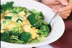 Cheesy Broccoli 1/2 lb.  (8 oz.) VELVEETA®, cut into 1/2-inch cubes 1/4 cup  milk 1/4 cup  finely chopped onions 1 clove  garlic, minced 5 cups  hot cooked broccoli florets make it  COMBINE all ingredients except broccoli in microwaveable bowl.  MICROWAVE on HIGH 3 min. or until VELVEETA is completely melted, stirring after each minute.  POUR over broccoli. Serve immediately.