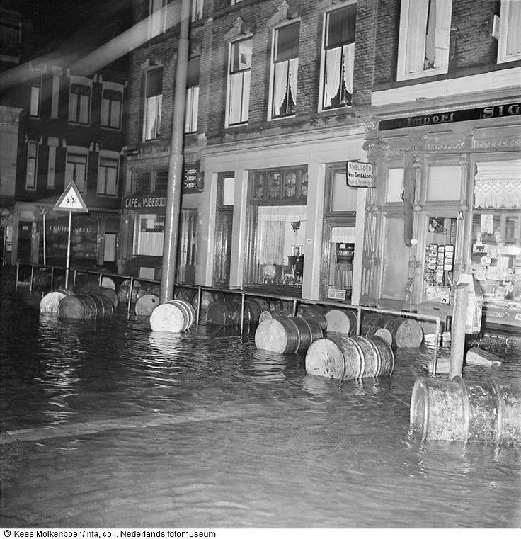 Ondergelopen Admiraliteitskade met ronddrijvende vaten bij avond in Rotterdam tijdens watersnoodramp (1953)