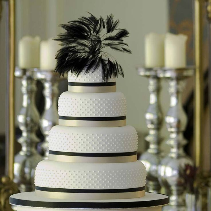 Art Deco artsy wedding cake..Feathers add instant glam to almost anything, as demonstrated by this four tiered cake from Not on the High Street! The black feather detail is a unique wedding cake topper and adds wow factor to an otherwise simple cake.