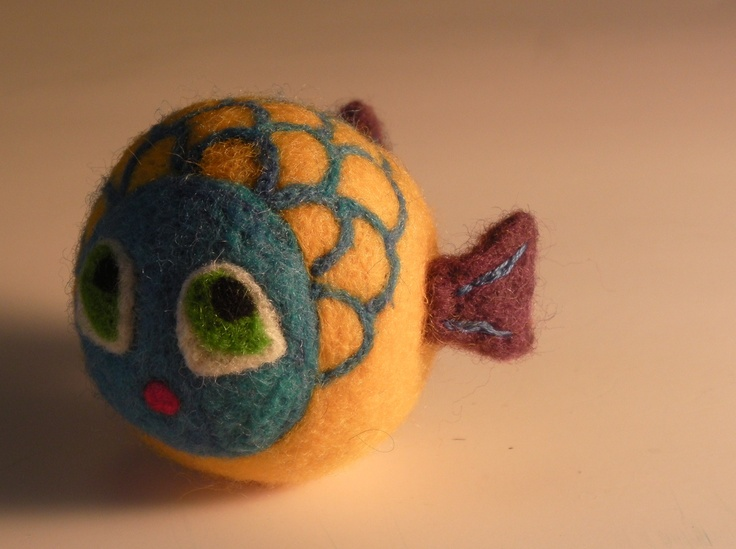 close up of a yellow felt fish with blue face and big green eyes.