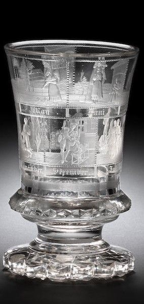 A North Bohemian engraved 'Monatebecher' by Anton Simm, Gablonz, circa 1830 The flared campana form decorated with two rows of six panels, each depicting a couple engaged in various activities allegorical of the months of the year, each titled, above a faceted band, set on a scalloped foot, the base cut with diamonds, 14.6cm high