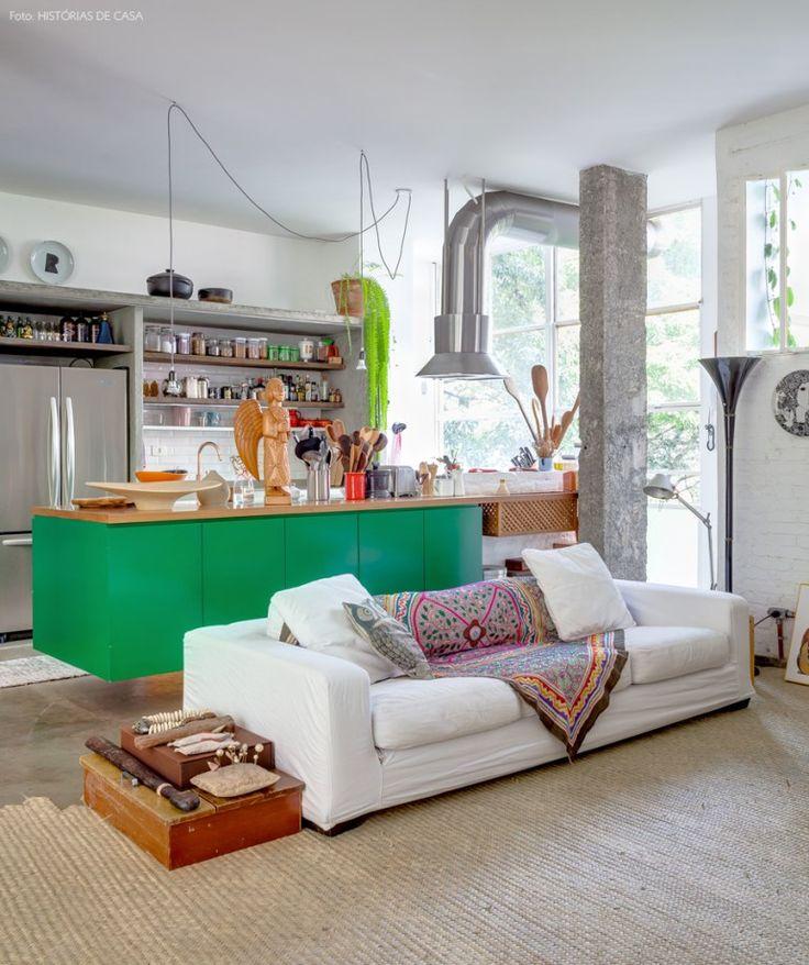 A cozinha integrada com a sala tem estrutura em concreto aparente e marcenaria na cor verde.