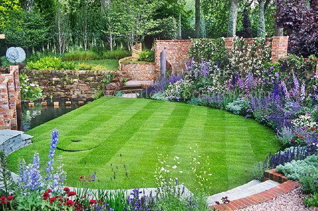 Show garden design based on the Golden Section. Perfect spiral lawn surrounded by curving brick wall, flowering perennial borders and water feature pool Merril Lynch Garden at RHS Chelsea Flower Show 2003 (Silver-Gilt Flora) Design: Xa Tollemache