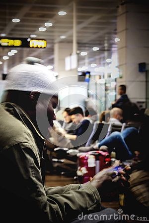 A black man is sitting at airport `Marco Polo` of Venice, and is using his smartphone while waiting to get on board of his airplane