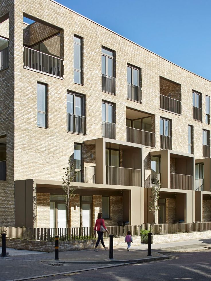 Bronze-coloured balconies project from trio of brick housing blocks by Alison Brooks Architects