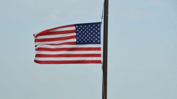 A US flag flies half-mast (Photo credit should read JEWEL SAMAD/AFP/Getty Images)