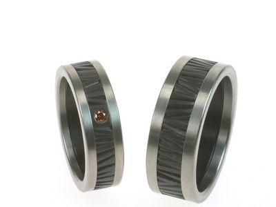 Trouwringen met structuur van boomschors. Prachtig gecombineerd met titanium ringen aan de zijkanten en een rode diamant.