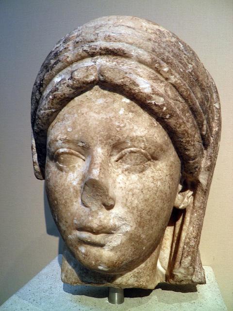 Tête en marbre d' une statue d'une prêtresse voilée de la déesse Vesta. Vesta est la déesse protectrice du foyer domestique et du foyer public, qui fut assimilé à la déesse grecque Hestia.Dans toute l'antiquité, le foyer était considéré comme le symbole de la vie domestique, dont le bonheur repose sur la chasteté de l'épouse. Plus tard elle devint la personnification du feu de la terre et même de la terre elle-même sous le nom de Vesta-Ops qu'on assimile à Cybèle ou à Gaia