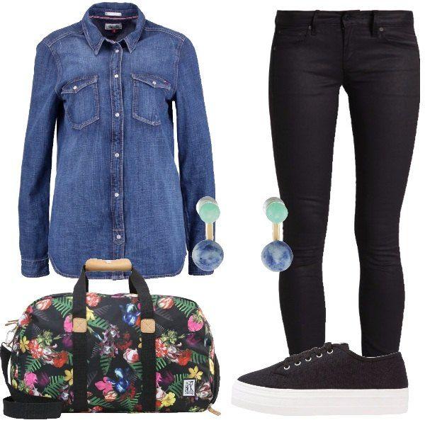 Look da giorno adatto per un viaggio, composto da camicia di jeans in blu denim e jeans neri skinny fit a vita bassa abbinati ad una sneakers nera in tela e ad una borsa da viaggio nera con fantasia floreale in tessuto, a completare il look orecchini a doppia perla blu e verde.
